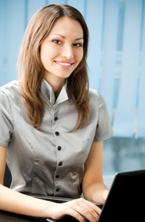 Young cheerful smiling business woman working with laptop at office photo