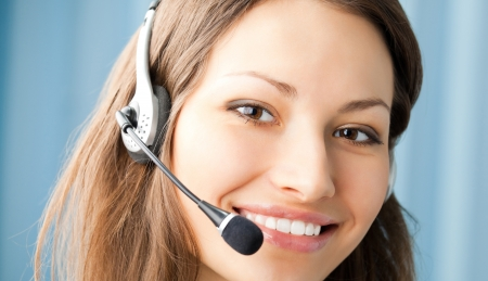 Young cheerful smiling support phone female operator in headset at office photo