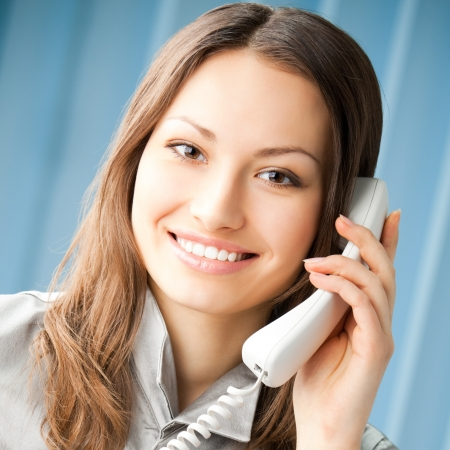 Young cheerful business woman with phone writing at office photo