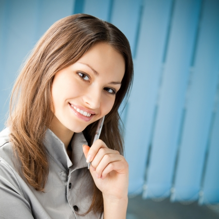 Young happy smiling cheerful business woman at office, with copyspace photo