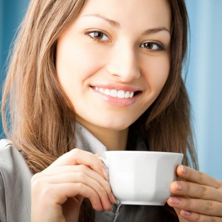 donna che beve il caff�: Allegro, sorridente, donna d'affari beve il caff� in ufficio