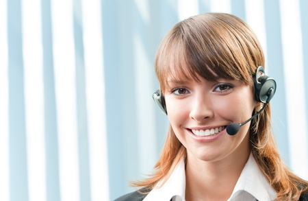 Young cheerful smiling support phone female operator in headset at office, with copyspace photo