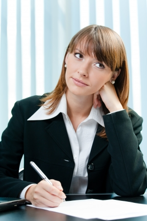 Young thinking business woman writing at office photo