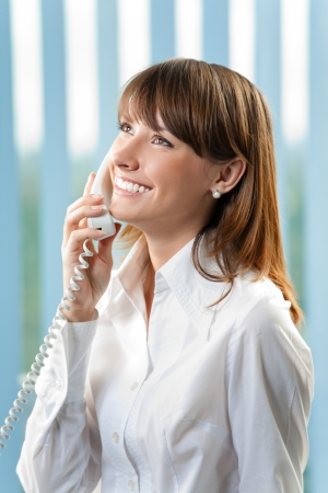 Young cheerful business woman with phone at office photo
