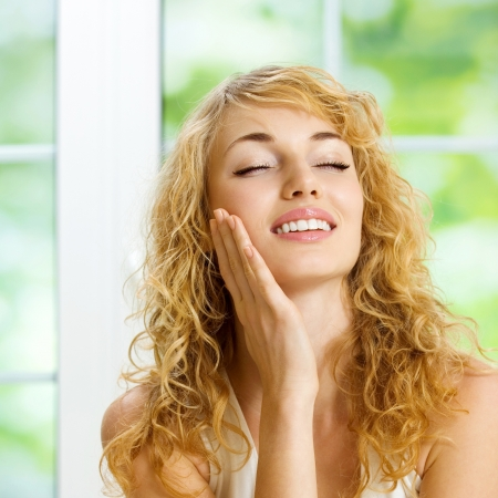 Portrait of young happy smiling cheerful beautiful blond woman applying creme, at home photo