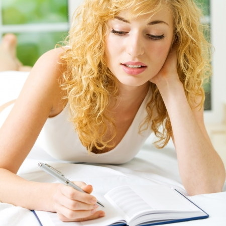Young beautiful blond woman studying with notebook or organiser, indoors photo