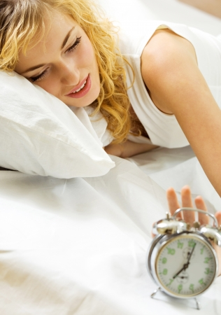 Blond beautiful woman with alarmclock on the bed  photo