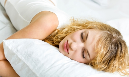 lazyness: Young beautiful blond woman sleeping on bed Stock Photo