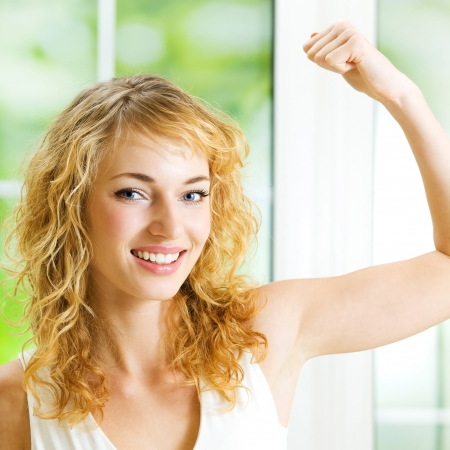 only the biceps: Cheerful young blond smiling woman showing biceps
