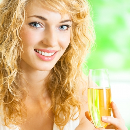 Portrait of young happy smiling cheerful beautiful blond woman with champagne photo