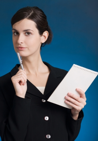 Portrait of happy smiling thinking business woman with blue notepad or organizer, over blue background photo