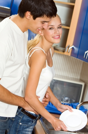 Young happy couple washing dishes at kitchen photo