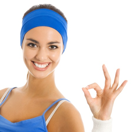 Portrait of beautiful smiling woman in fitness wear showing OK sign, isolated over white background photo