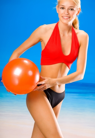 Young happy smiling cheerful beautiful woman in sportswear playing with red ball on beach photo