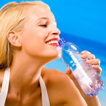 Portrait of beautiful happy woman with bottle of water on beach photo