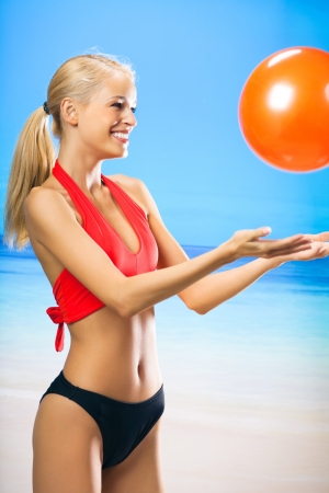 Young happy smiling cheerful beautiful woman in sportswear playing with red ball on beach Stock Photo - 14870695