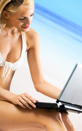 Young happy smiling woman with laptop, working, chatting, searching or walking by mobile internet on beach photo