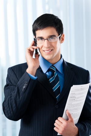 Happy young business man with cellphone and documents, at office photo