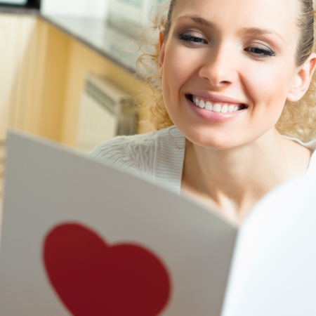 Cheerful smiling young woman, reading valentine card photo