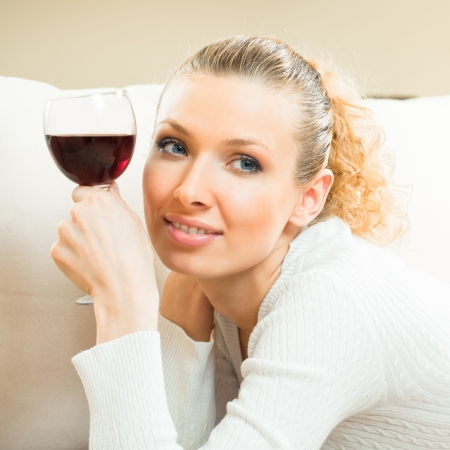 winetasting: Portrait of young happy smiling cheerful beautiful blond woman with glass of red wine