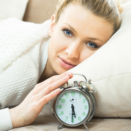 Young blond woman with alarmclock on the bed at the morning photo