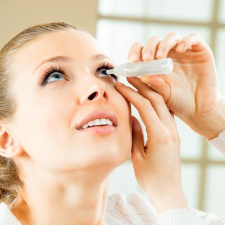 eye in eye: Woman dripping eye with eyes drops