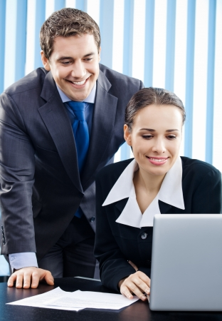 Two happy smiling cheerful young businesspeople working with laptop at office photo