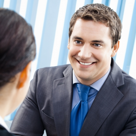 Two cheerful smiling young businesspeople, or business man and client, working at office photo