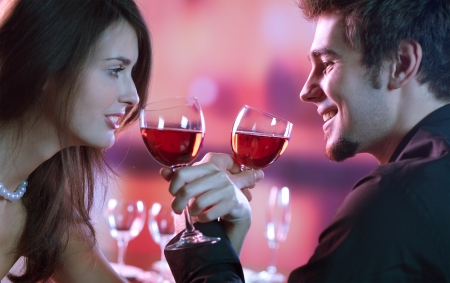 flirtation: Young happy amorous couple with glasses of redwine on romantic date at restaurant