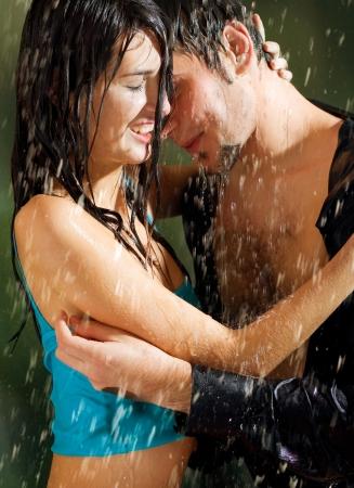 man and woman sex: Молодая счастливая пара любовных объятий под дождем, на улице