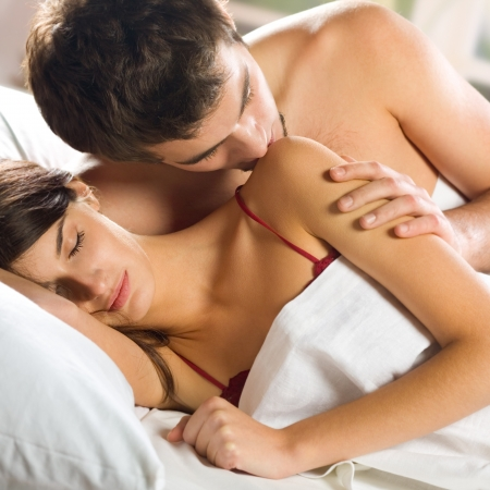 Young beautiful amorous couple making love in bed Stock Photo - 15025562