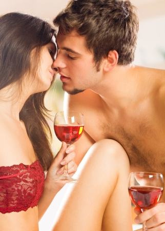 Young happy couple celebrating with red wine at bedroom photo