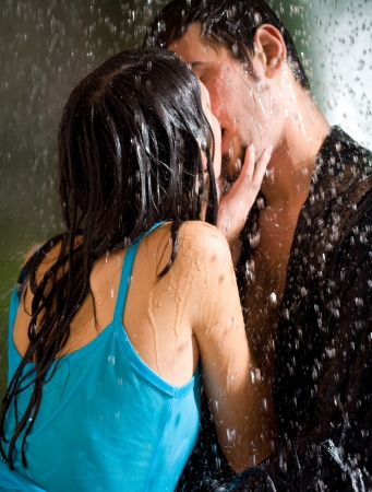 Young happy amorous couple hugging and kissing under a rain, outdoors Stock Photo - 15025621