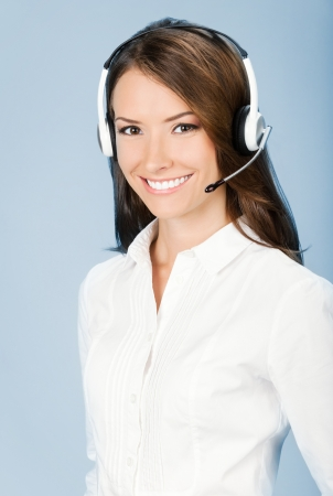 Portrait of happy smiling cheerful customer support phone operator in headset, over blue background Stock Photo - 15025626