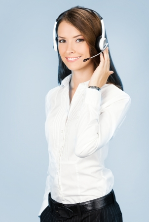 hotline: Portrait of happy smiling cheerful customer support phone operator in headset, over blue background