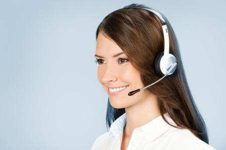 hands free phone: Retrato de feliz sonriente operador de tel�fono de atenci�n al cliente alegre en auriculares, sobre fondo azul
