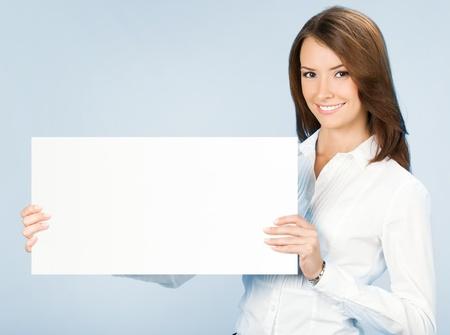 Happy lachende jonge zakenvrouw met lege uithangbord, op blauwe achtergrond