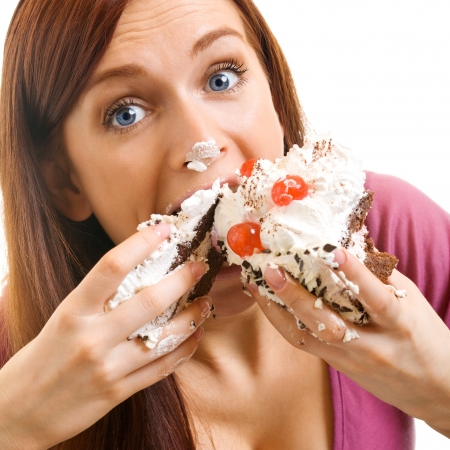 unhealthy eating: Cheerful woman eating pie, isolated over white background Stock Photo
