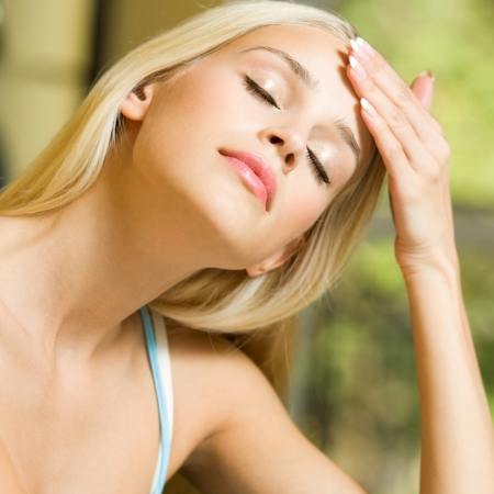 Portrait of young blond woman with headache or applying creme Stock Photo - 15068817