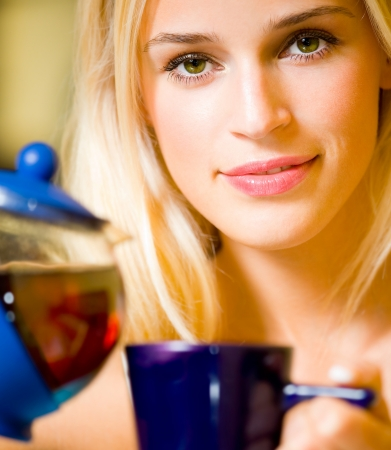 Happy smiling cheerful blond girl with teapot and cup, at home photo