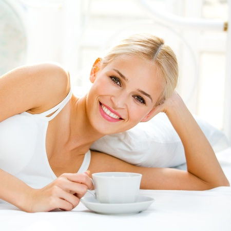 wake up happy: Happy smiling beautiful blond woman awaking with cup of coffee at bedroom