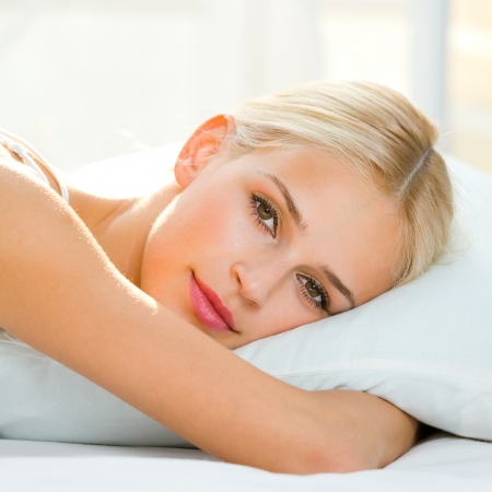 Young beautiful happy smiling blond woman waking up on bed  photo