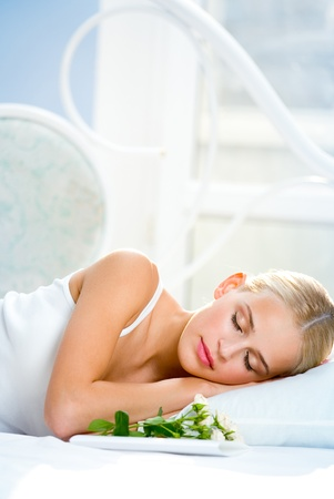 Young sleeping blond woman with bouquet of roses and valentine card on bed  photo
