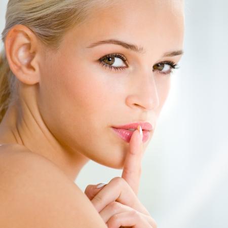 guardar silencio: Retrato de la mujer rubia hermosa con el dedo en los labios