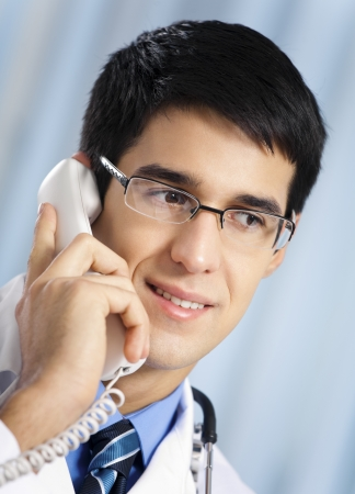 Portrait of happy smiling cheerful young doctor on phone, at office photo