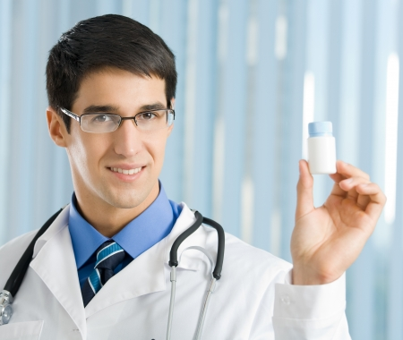 Happy smiling cheerful young doctor showing bottle of drugs, at office photo