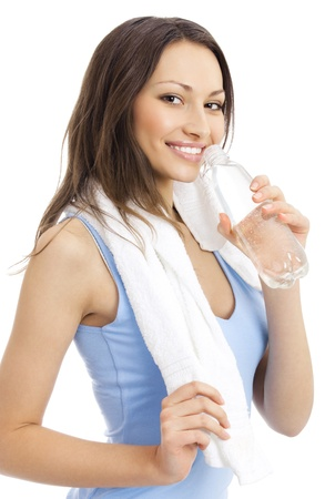 sports wear: Happy smiling young woman in fitness wear with bottle of water, isolated over white background Stock Photo