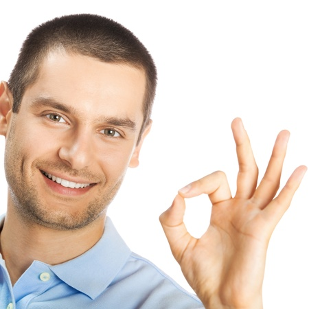 alright: Portrait of cheerful young man showing okay gesture, isolated over white background
