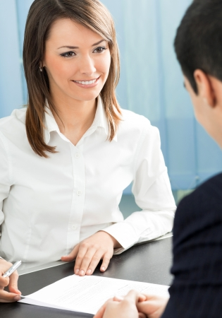 women talking: Two cheerful smiling young businesspeople, or business woman and client, working at office Stock Photo