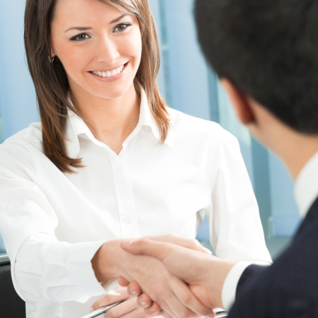 businessmen shaking hands: Cheerful businesspeople, or businesswoman and client handshaking Stock Photo